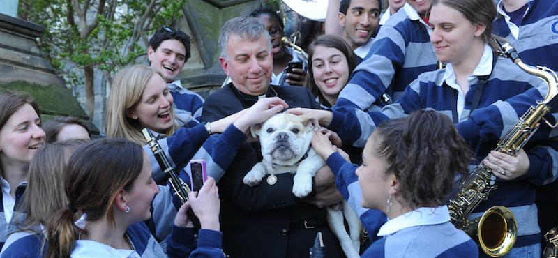 Father Steck holds Jack the Bulldog, surrounded by smiling members of the Georgetown Marching Band
